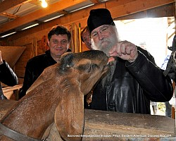 Bishop George feeds<br/> one of the monastery goats. Fall 2011