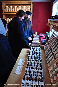 Fr.Alexander shows <br/>monastery merchandise to a visitor.