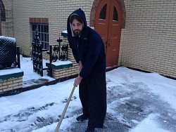 Br. Leo cleans snow in front of the monastery's<br/> main church
