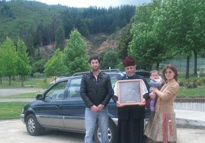 Fr Alexei and his family<br/>pose in front of the new car