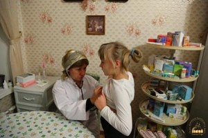 A nurse examines a young refugee at Svyatogorsk Lavra.