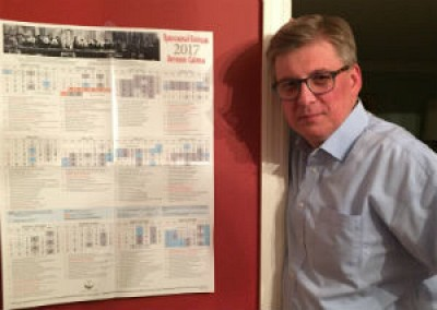 Peter Fekula poses in front of the 2017 Liturgical Calendar he was responsible for putting together.