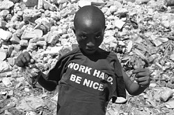 Haitian boy poses with a T-shirt<br>saying 'Work hard. Be nice'.<br>Photo: Serge McKenzie